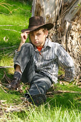 boy sitting against a tree in the Australian outback